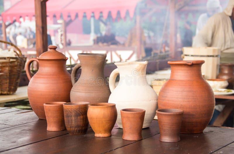 酒水罐和套在木桌上的黏土杯子 免版税库存图片