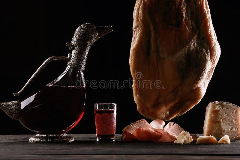 酒玻璃水瓶以鸭子、一杯酒,帕尔马火腿的腿和乳酪的形式 库存照片