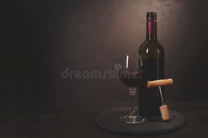 酒瓶、玻璃与红酒和黄柏与拔塞螺旋在黑暗的木背景 庆祝概念查出的白色 复制空间 定调子 库存图片