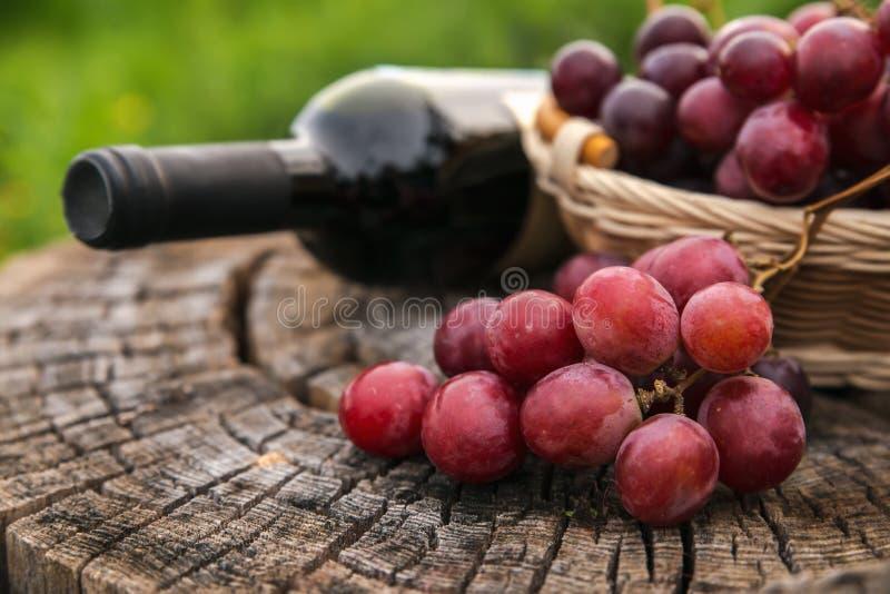 酒瓶和篮子用葡萄在老木背景 库存照片