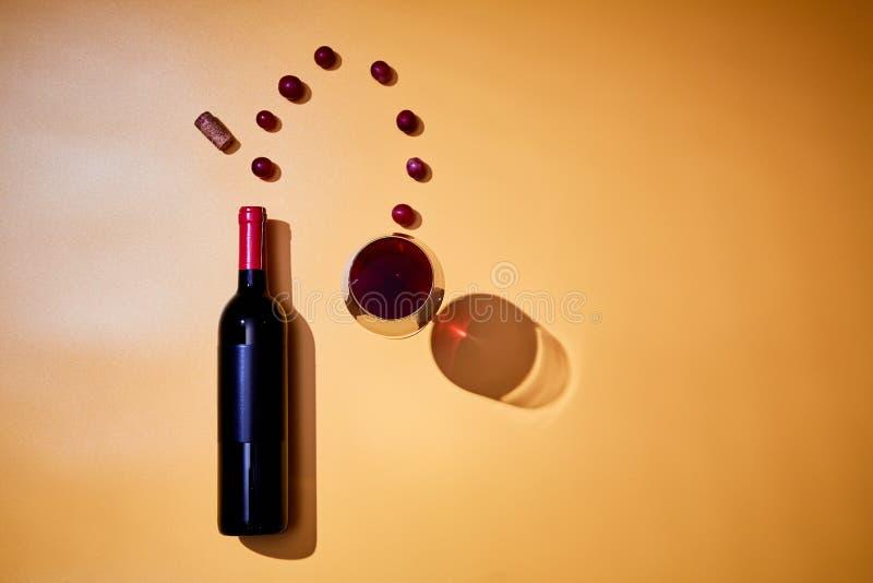 酒瓶和飞行的葡萄布局到杯红酒里在黄色背景 免版税图库摄影