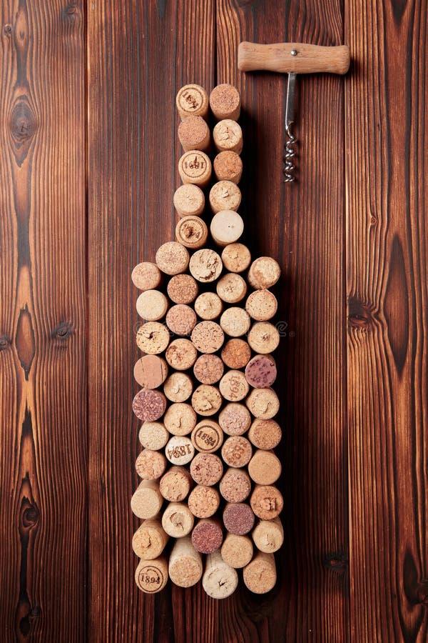 酒瓶塑造了黄柏和拔塞螺旋在土气木桌背景和粗麻布 与拷贝空间-图象的顶视图 库存图片