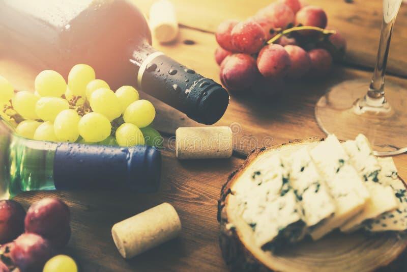 酒瓶葡萄和乳酪在老木桌上 免版税图库摄影
