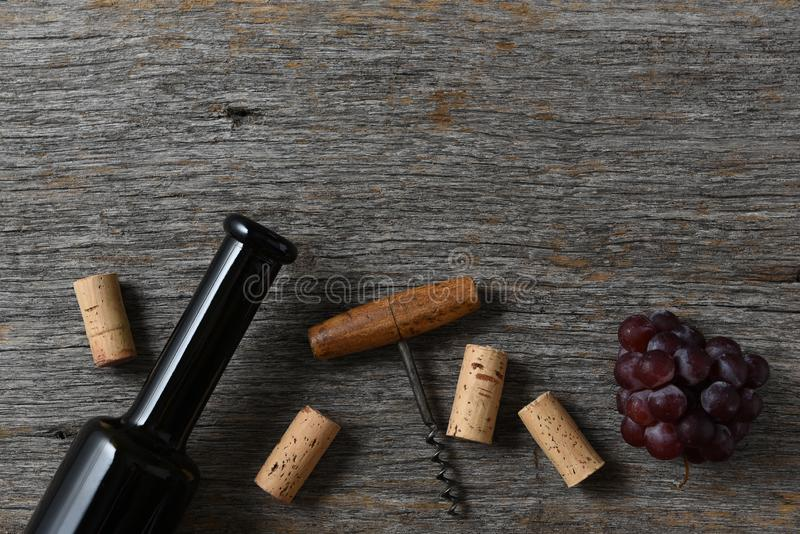 酒瓶黄柏、拔塞螺旋和葡萄在一张土气老木桌上,与拷贝空间在上面 库存图片