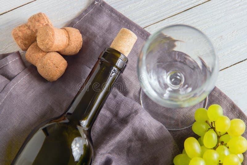 酒瓶,玻璃,在桌上的葡萄 顶视图 免版税库存图片