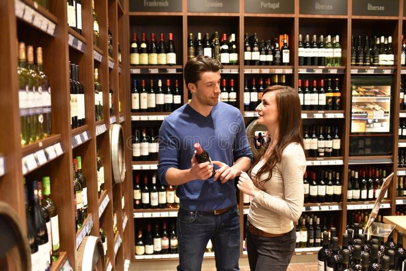 酒的年轻幸运的夫妇购物在超级市场 免版税库存照片