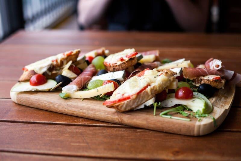 酒的开胃菜在贝尔格莱德,塞尔维亚:heese Ñ的,烟肉,橄榄,芝麻菜,樱桃, bruschetta 免版税库存照片