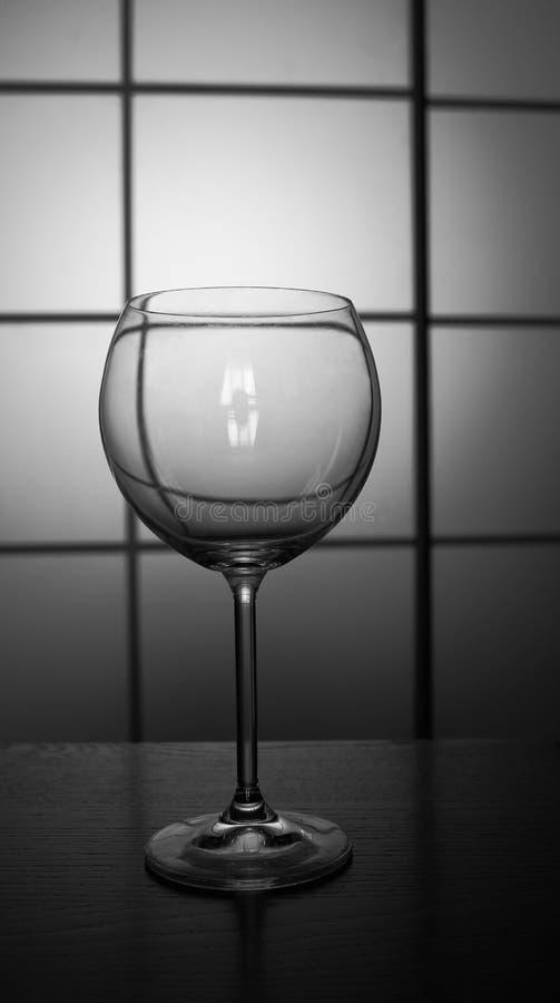 酒的空的在桌上隔绝的玻璃和champain反对被摆正的背景黑白黑白照片 免版税库存照片