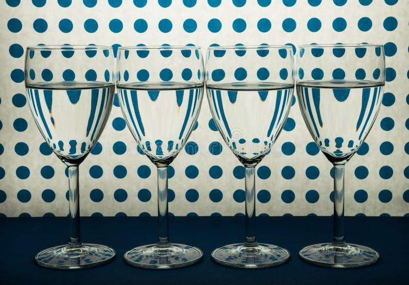 酒站在队中和白色背景的四块透明玻璃与蓝色斑点 免版税库存图片