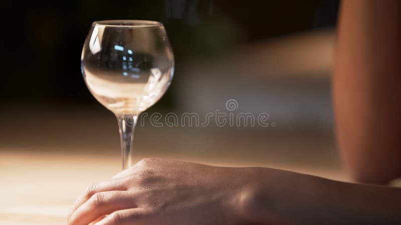 酒站立在桌上的妇女感人的透明杯在咖啡馆,特写镜头 免版税库存照片