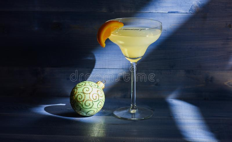 酒精与橙色近的圣诞节球装饰品片断的鸡尾酒玛格丽塔酒在深蓝背景的 庆祝新年度 库存图片