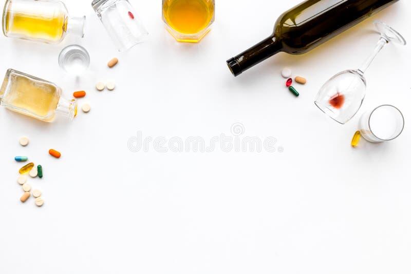 酒精中毒治疗 玻璃、瓶和药片在白色背景顶视图拷贝空间 免版税库存图片