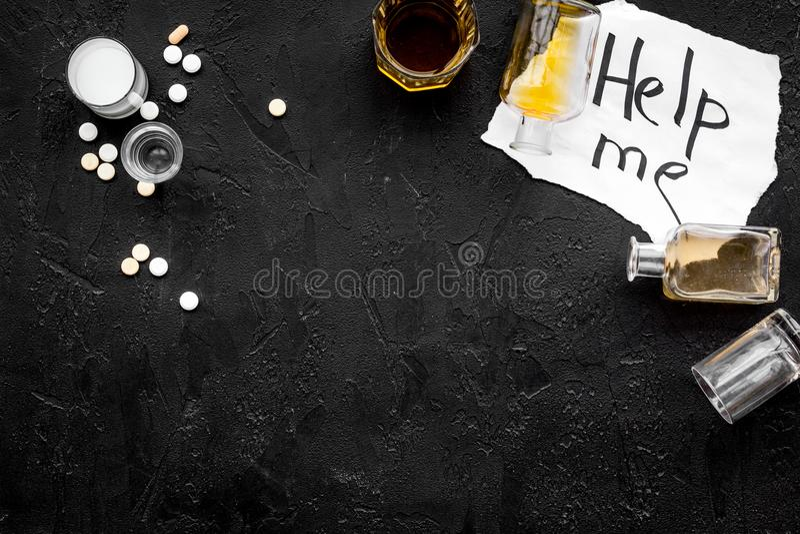 酒精中毒治疗 玻璃、瓶和药片 在上写字在黑背景顶视图拷贝空间帮助我 免版税库存图片