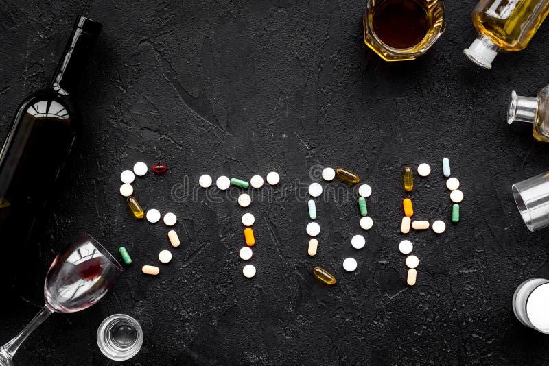 酒精中毒治疗 玻璃、瓶和药片 措辞在黑背景顶视图拷贝空间的中止 免版税库存照片