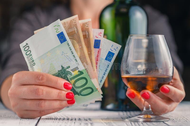 酒精中毒问题 在黑暗的被定调子的桌上的女性作为酒杯 库存图片