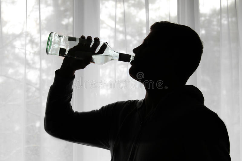 酒精中毒-人饮用的酒精剪影  免版税库存照片
