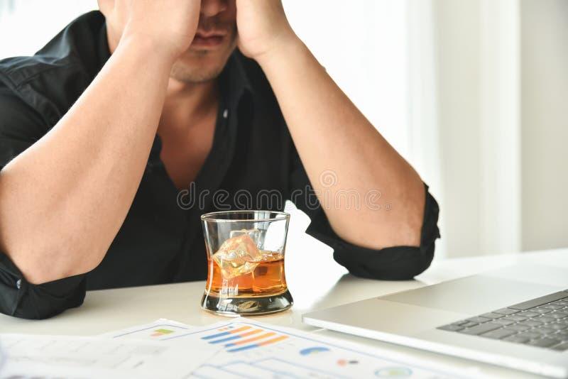 酒精使上瘾的商人拿着威士忌酒玻璃 免版税图库摄影