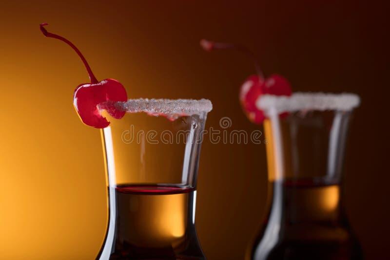 酒精分层了堆积射击鸡尾酒装饰用樱桃和糖 免版税图库摄影