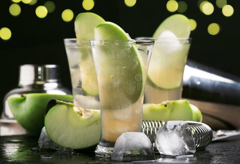 酒精鸡尾酒用干白色苦艾酒、绿色苹果、汁液、苏打和冰,黑酒吧柜台背景,选择聚焦 库存图片