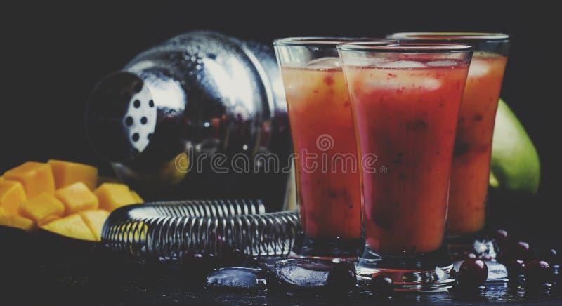 酒精鸡尾酒芒果和蔓越桔利口酒用糖浆,汁液 免版税库存图片