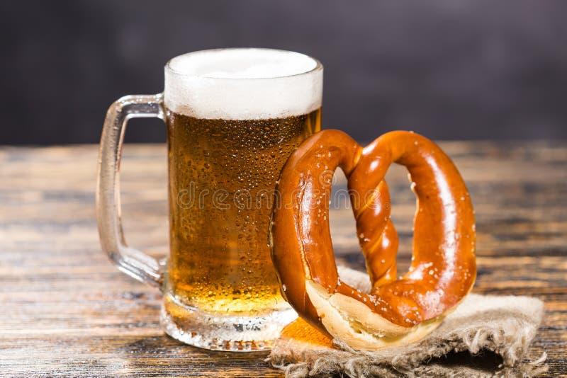 酒精,液体,食物概念-一个巨大的杯子在一张桌上的啤酒用百吉卷 库存照片