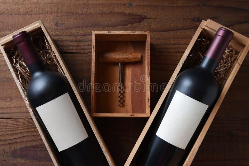酒静物画:有一个瓶的两个木酒箱子有空白的标签的 在箱子之间是一个小盒子和一个古色古香的黄柏螺丝 免版税图库摄影