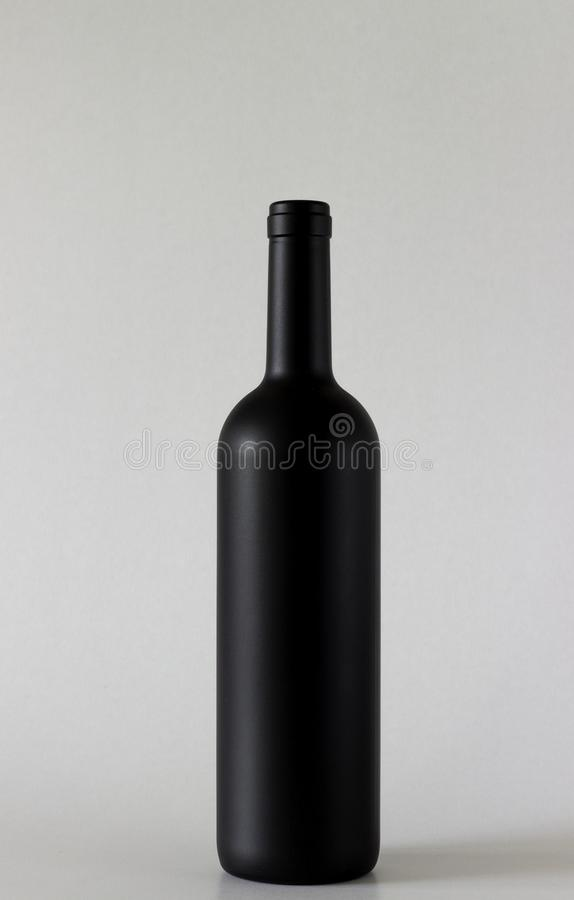 酒黑瓶在灰色背景站立 免版税图库摄影