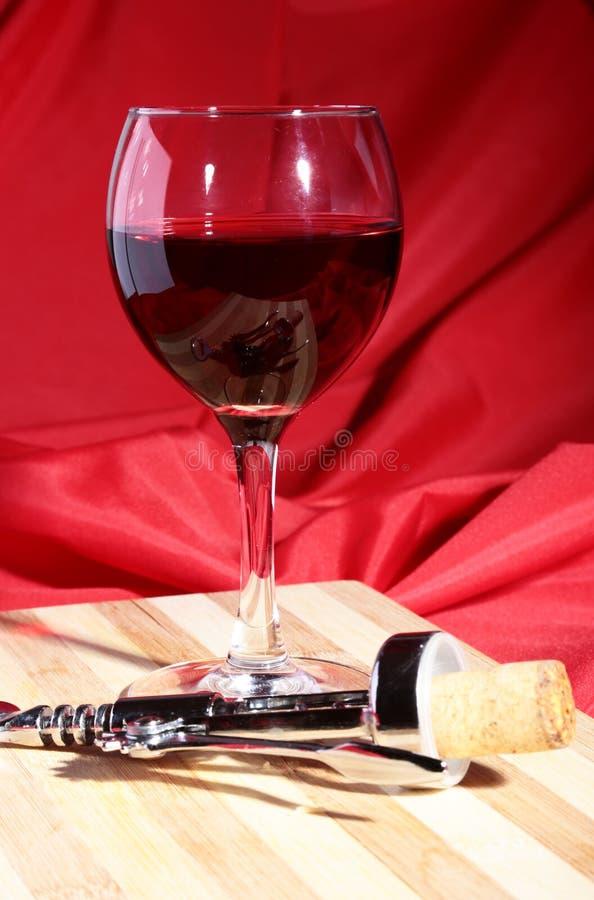 酒黄柏、拔塞螺旋和玻璃用红葡萄酒葡萄在木桌上 库存图片