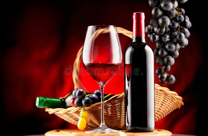 酒 瓶和杯红葡萄酒用成熟葡萄 图库摄影