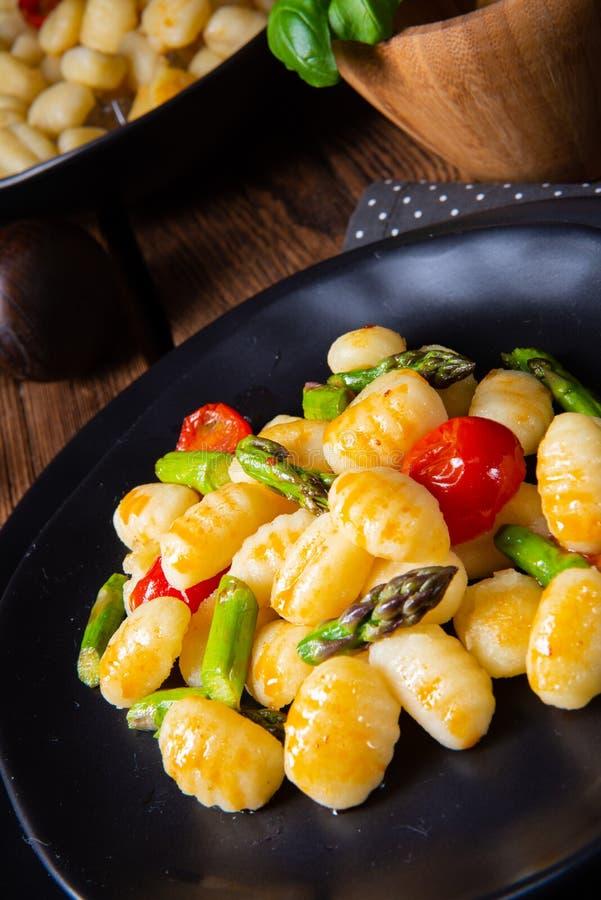 酥脆尼奥基用烤芦笋和蕃茄 库存照片