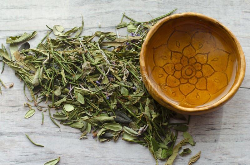 酥脆茶用常春藤茶,番红花,蓝莓叶子  陶瓷杯子手工制造与与装饰品坛场的红土 库存照片