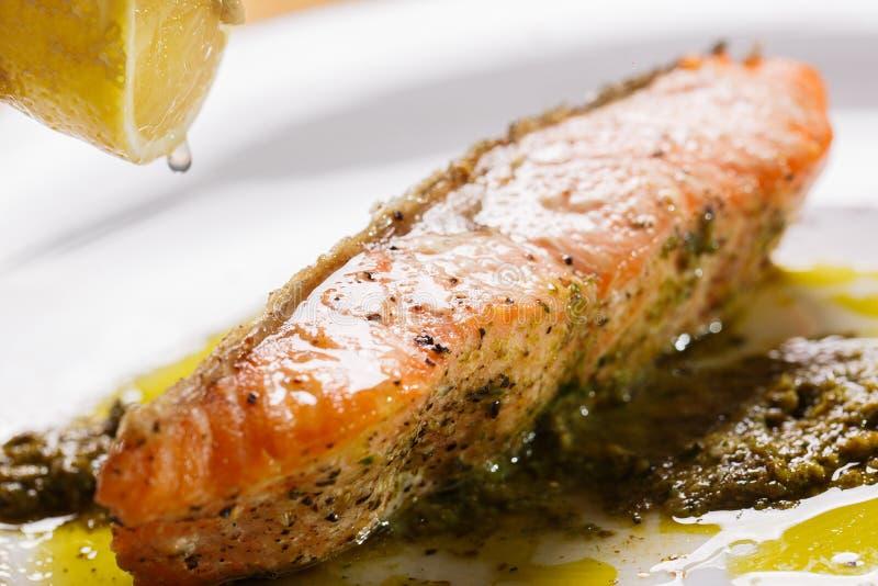 酥脆鲑鱼排用冠上下落柠檬的pesto调味汁 库存照片