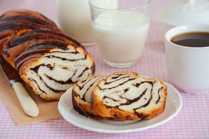 酵母卷用巧克力和罂粟种子用茶和牛奶 免版税库存图片