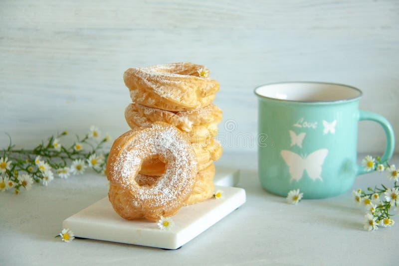 酸奶干酪在有小白花和蓝色茶杯的一个白板敲响 图库摄影