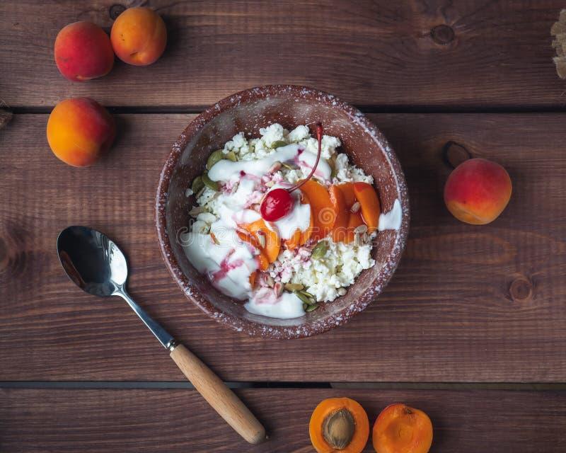 酸奶干酪早餐用新鲜的杏子和樱桃在一块深陶瓷板材在一张木桌上,采取从上部角度 图库摄影