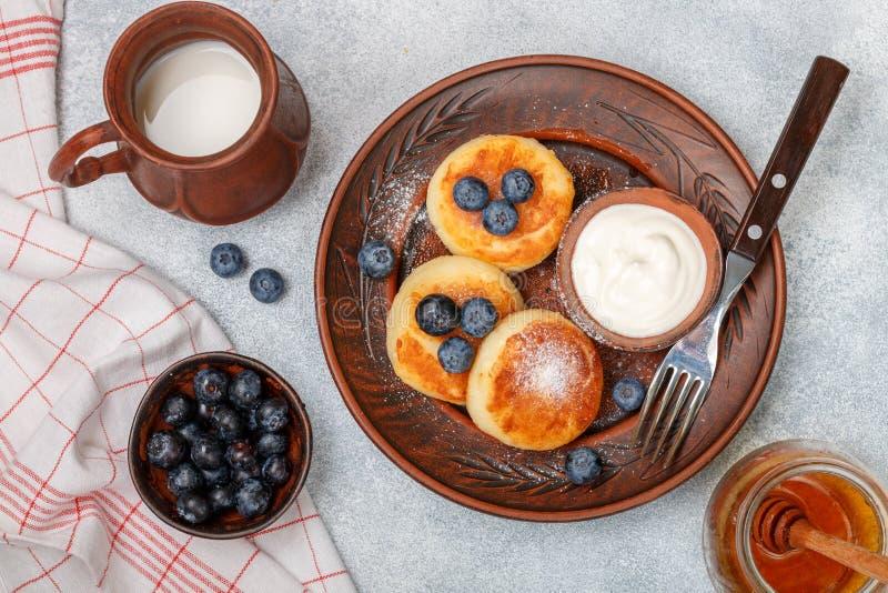 酸奶干酪薄煎饼、syrniki、凝乳油炸馅饼用新鲜的莓果蓝莓,糖粉、牛奶、蜂蜜和酸性稀奶油 免版税库存照片