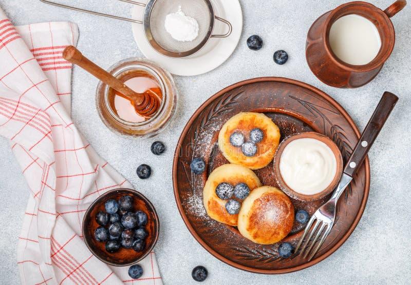 酸奶干酪薄煎饼、syrniki、凝乳油炸馅饼用新鲜的莓果蓝莓,糖粉、牛奶、蜂蜜和酸性稀奶油 免版税库存图片