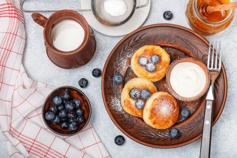 酸奶干酪薄煎饼、syrniki、凝乳油炸馅饼用新鲜的莓果蓝莓,糖粉、牛奶、蜂蜜和酸性稀奶油 免版税图库摄影