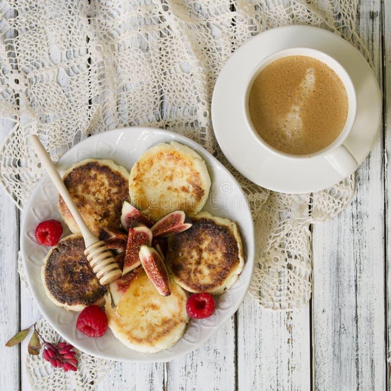 酸奶干酪薄煎饼用新鲜的无花果和蜂蜜和杯子ofcoffee早餐 免版税库存照片