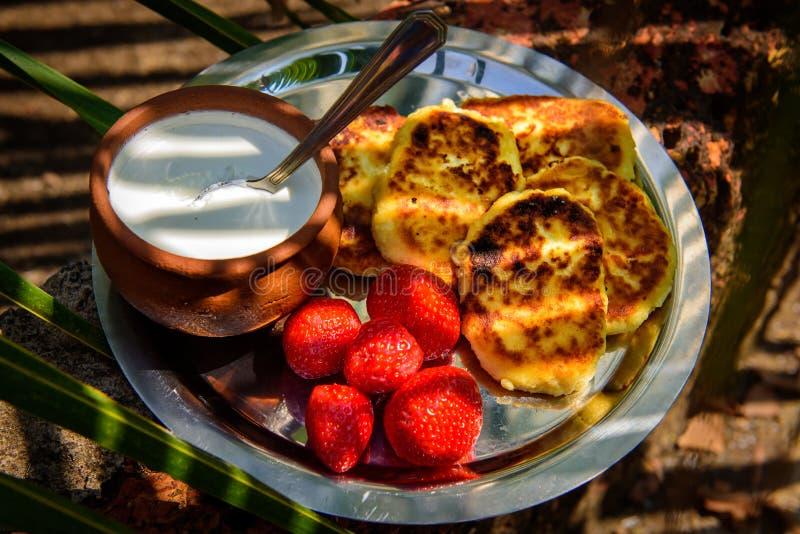 酸奶干酪薄煎饼/syrniki/凝乳油炸馅饼用新鲜的草莓和奶油 传统乌克兰和俄国早餐 免版税图库摄影