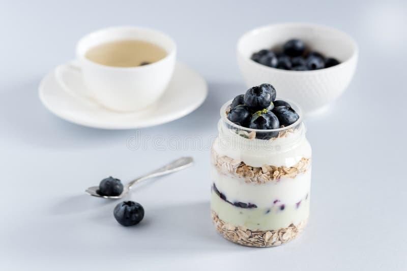 酸奶服务与整个新鲜的蓝莓燕麦粥和Matcha粉末健康饮食食物早餐茶的 免版税库存图片