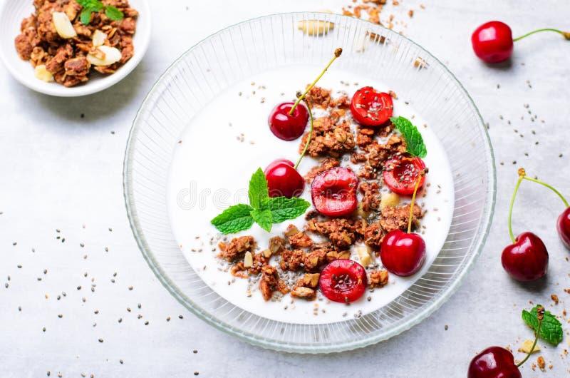 酸奶用樱桃、格兰诺拉麦片和Chia种子在明亮的背景 免版税库存图片