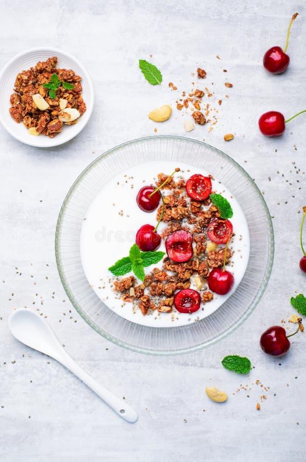 酸奶用樱桃、格兰诺拉麦片和Chia种子在明亮的背景 库存图片