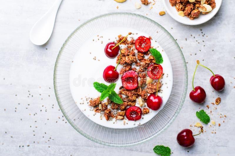酸奶用樱桃、格兰诺拉麦片和Chia种子在明亮的背景 免版税库存照片
