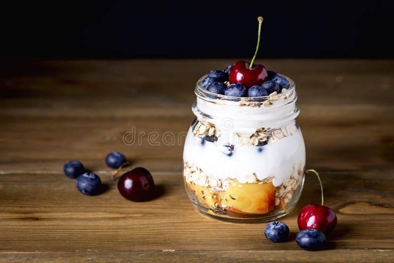 酸奶用燕麦粥果子和莓果健康饮食早餐土气黑暗的照片木背景拷贝空间 库存图片