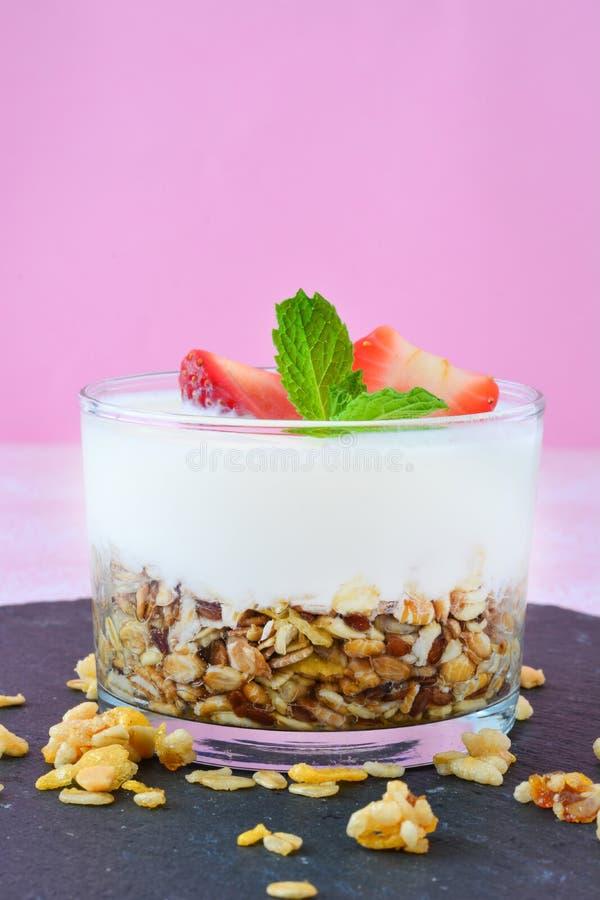酸奶玻璃用谷物和草莓,桃红色背景 免版税图库摄影