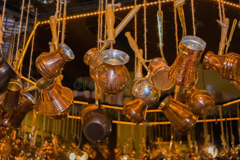 酿造咖啡吊的铜土耳其人在柜台在商店 免版税库存照片