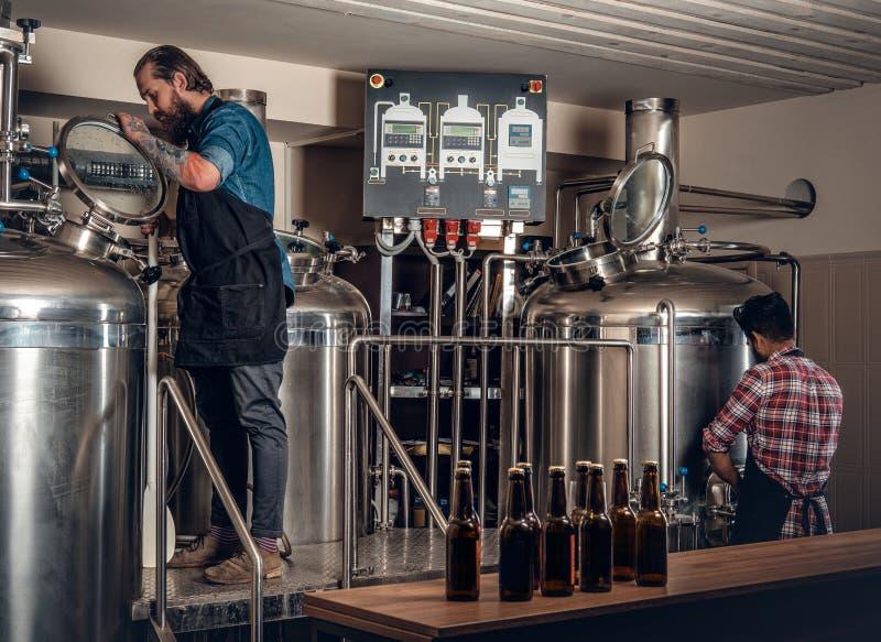 酿造啤酒的两个人在工艺microbrewery 库存照片