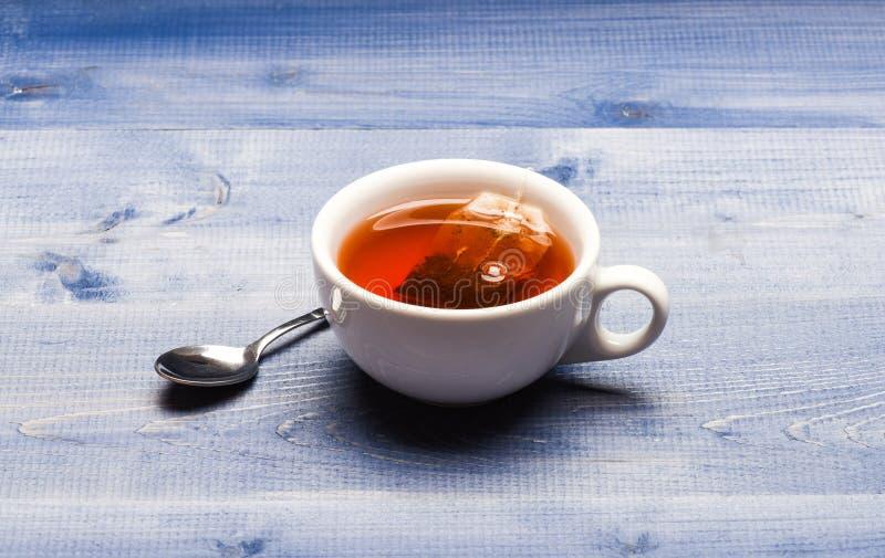 酿造在杯子的红茶的过程 杯子用开水、茶袋和匙子填装了在蓝色木纹理背景 免版税库存图片