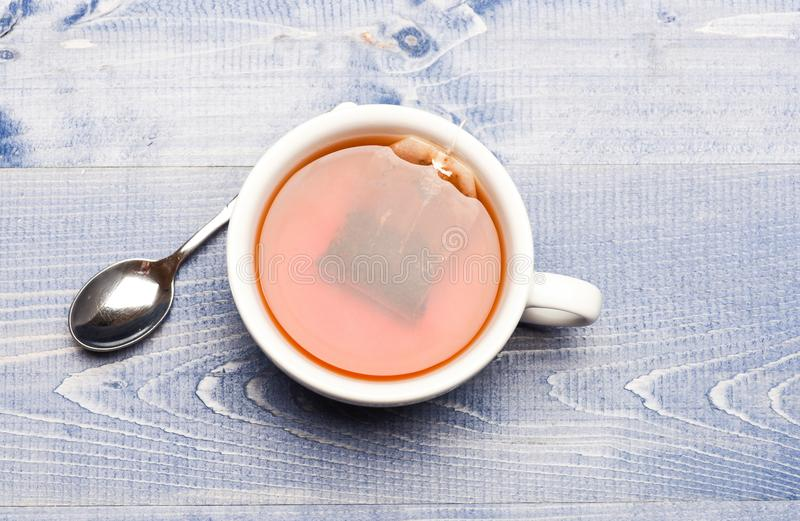 酿造在杯子,顶视图的红茶的过程 杯子用开水、茶袋和匙子填装了在木纹理 免版税图库摄影
